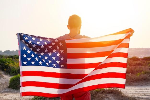 Vista traseira do homem segurando acenando a bandeira americana dos eua contra o céu do sol ao ar livre. dia da independência dos estados unidos da américa. conceito de povo patriótico americano