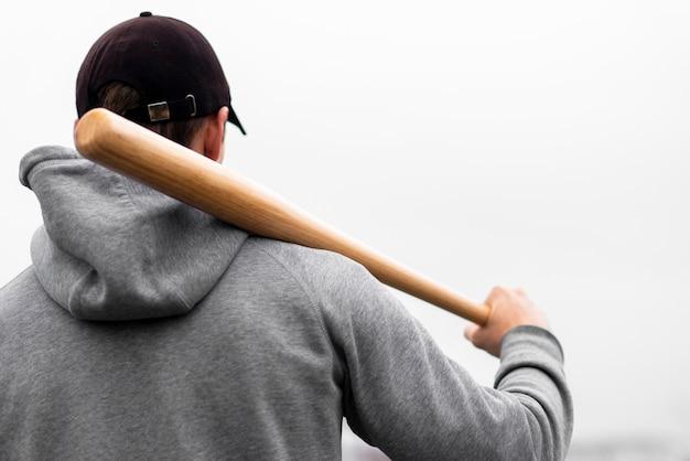Vista traseira do homem segurando o taco de beisebol no ombro