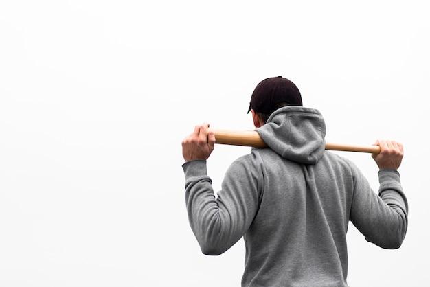 Vista traseira do homem segurando o taco de beisebol nos ombros