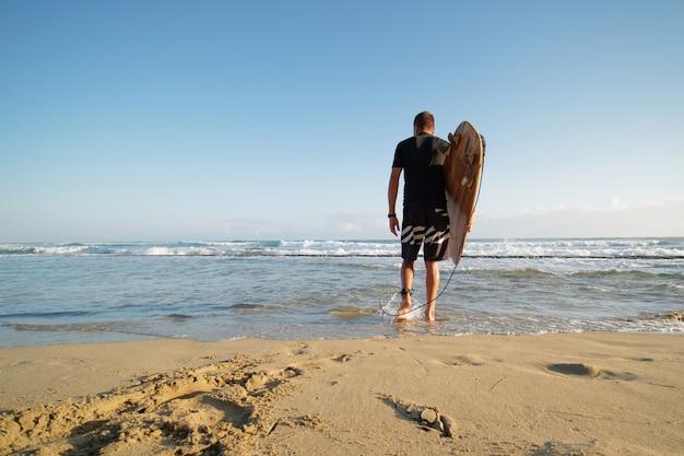 Vista traseira do homem surfista com prancha de surf para o oceano. estilo de vida.