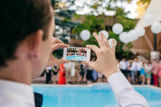Vista traseira do homem tirando uma foto do grupo de pessoas em uma festa