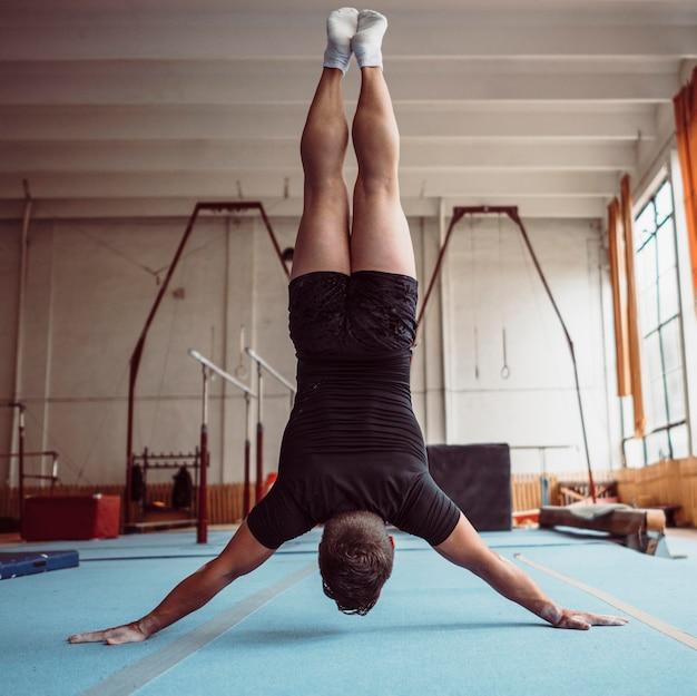 Vista traseira do homem treinando com barras paralelas
