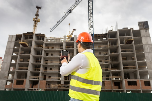 Vista traseira do inspetor de construção segurando um tablet digital e inspecionando o canteiro de obras