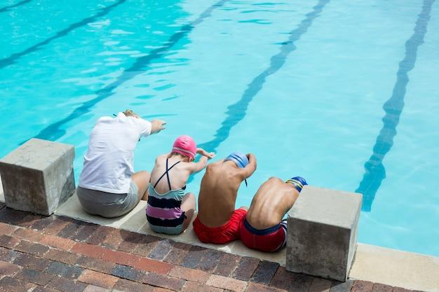 Vista traseira do instrutor de natação com os alunos ao lado da piscina