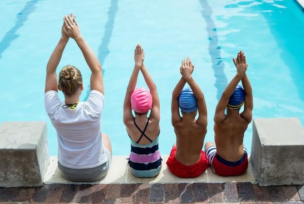Vista traseira do instrutor de natação ensinando crianças ao lado da piscina