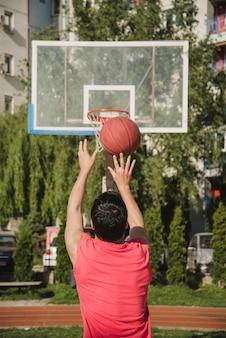 Vista traseira do jogador de basquete jogando