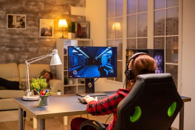 Vista traseira do jogador feminino jogando no poderoso computador pc tarde da noite na sala de estar.