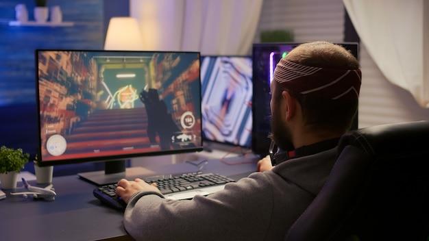 Vista traseira do jogador profissional sentado na cadeira de jogos na mesa e jogando videogame de tiro em primeira pessoa no computador poderoso. torneio de jogo online com streaming de jogador digital com luzes de néon rgb