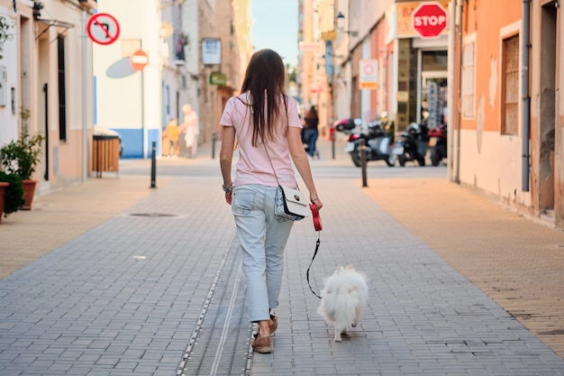 Vista traseira do jovem andando com um pomeranian fofo branco.