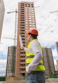 Vista traseira do jovem arquiteto apontando com plantas para o prédio em construção