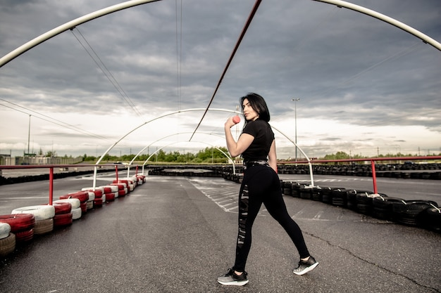 Vista traseira do jovem atlética fazendo exercícios com halteres no playground ao ar livre após a quarentena covid-19. cuidados de saúde, conceito de esportes