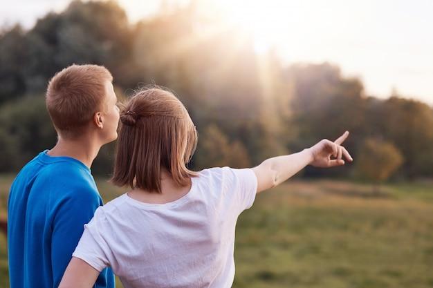 Vista traseira do jovem casal afetuoso fica de perto, admira a natureza, vê algo distante, aprecia o pôr do sol, copia o espaço de lado.
