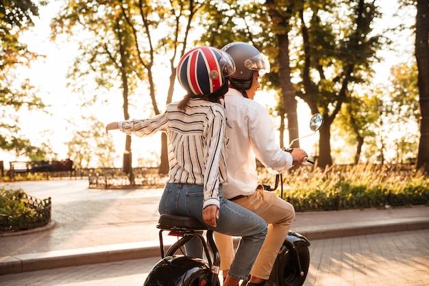 Vista traseira do jovem casal africano passeios de moto moderna no parque