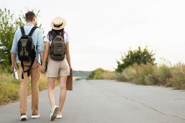 Vista traseira do jovem casal caminhando pela estrada