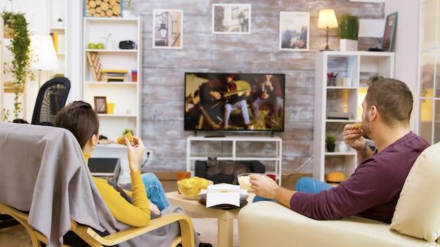 Vista traseira do jovem casal comendo frango frito, sentado confortável em suas cadeiras, olhando para a tv. gato relaxando em sua cama aconchegante.