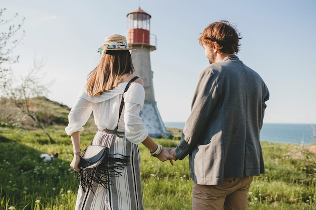 Vista traseira do jovem casal hippie estilo indie apaixonado caminhando pelo campo, de mãos dadas, farol no fundo, dia quente de verão, ensolarado, roupa boêmia, chapéu