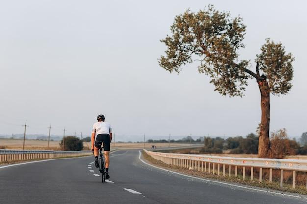 Vista traseira do jovem ciclista em roupas esportivas e capacete protetor andando em estrada asfaltada durante o dia de verão