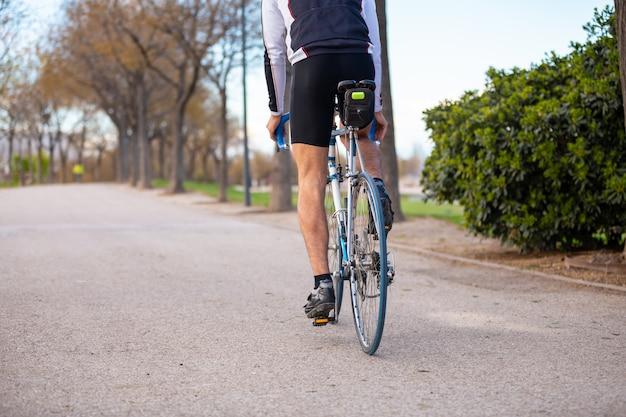 Vista traseira do jovem ciclista masculina em sportswear e capacete protetor, bicicleta de bicicleta na estrada no parque