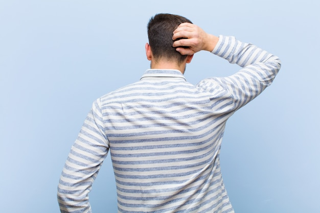 Vista traseira do jovem coçando a cabeça