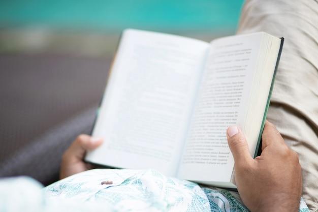 Vista traseira do jovem com roupas casuais, abrindo e lendo um livro e relaxando enquanto estava deitado no sofá à beira da piscina.
