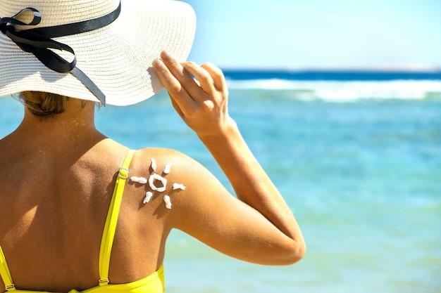Vista traseira do jovem de bronzeamento na praia com creme protetor solar em forma de sol no ombro dela. proteção contra queimaduras uv e conceito de protetor solar