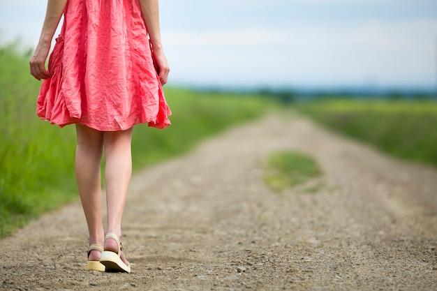 Vista traseira do jovem em pernas de vestido vermelho, andando pela estrada de chão num dia de verão