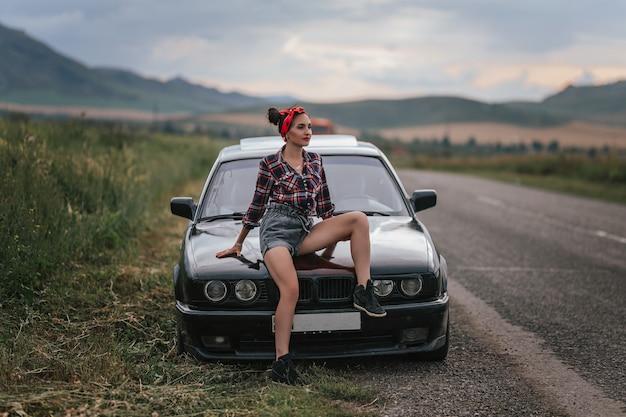 Vista traseira do jovem em shorts jeans curto cinza está consertando o carro. em shorts perto de um carro preto com o capô aberto. problemas com o carro na viagem. morena reparando o motor