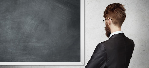 Vista traseira do jovem empregado usando óculos e terno formal, em frente ao quadro-negro, apresentando algo.