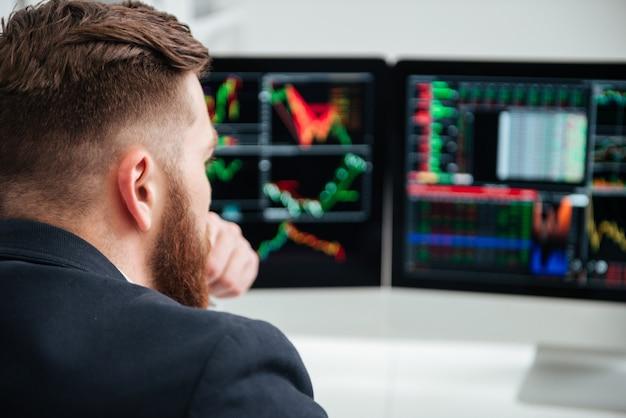 Vista traseira do jovem empresário concentrado pensando e trabalhando no escritório