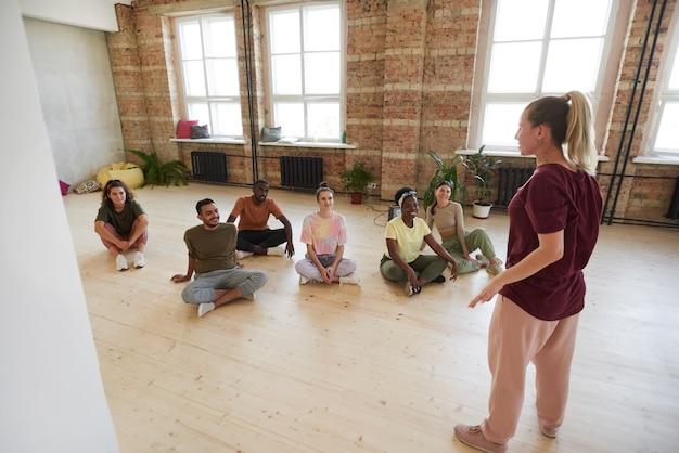 Vista traseira do jovem instrutor falando com sua equipe antes do treinamento esportivo no estúdio de dança