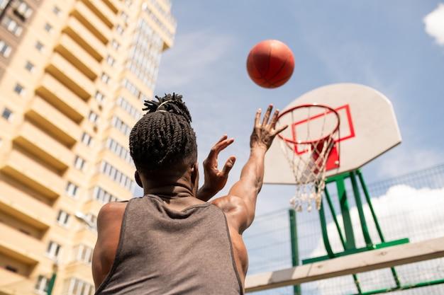 Vista traseira do jovem jogador de basquete africano jogando bola na cesta durante o treinamento em ambiente urbano