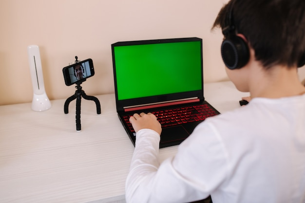 Vista traseira do jovem jogador jogando na tela verde do laptop