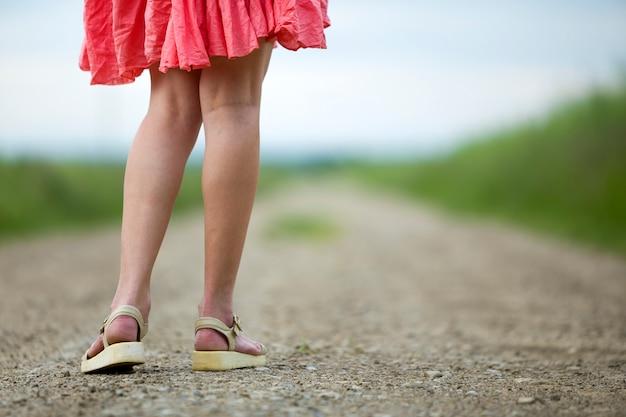 Vista traseira do jovem nas pernas de vestido vermelho, andando pela estrada de terra num dia de verão no ensolarado turva.