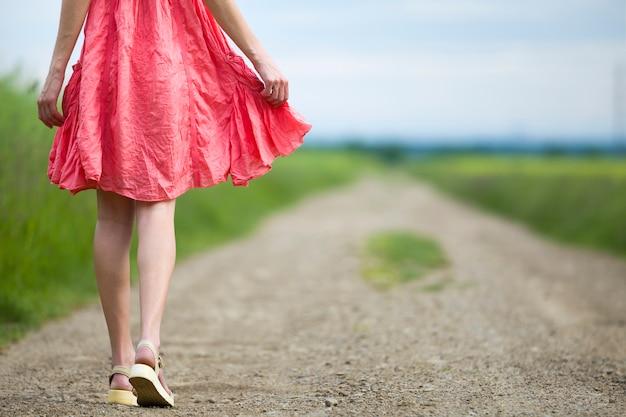 Vista traseira do jovem nas pernas de vestido vermelho, andando pela estrada de terra num dia de verão no fundo desfocado ensolarado.