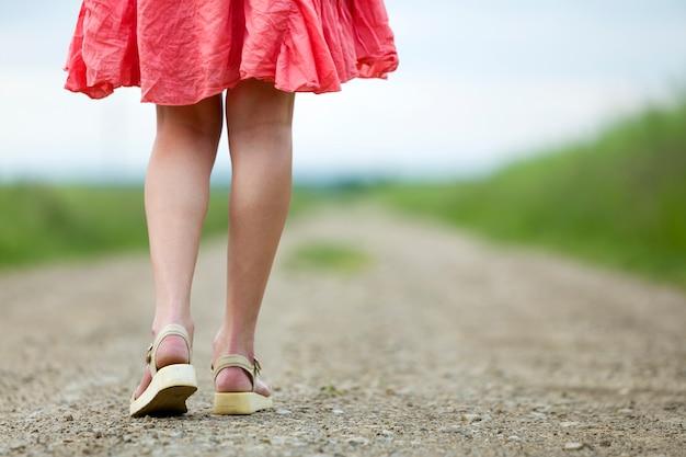 Vista traseira do jovem nas pernas do vestido vermelho andando pela estrada de terra num dia de verão no ensolarado turva.