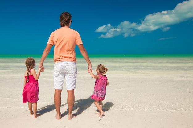 Vista traseira do jovem pai e suas duas filhas adoráveis em umas férias exóticas