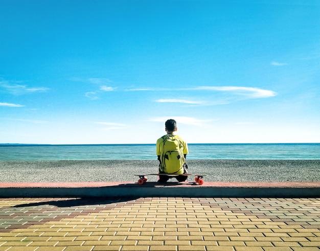 Vista traseira do jovem patinador sentado e relaxando em um longboard ou skate na praia no mar e no fundo do céu azul