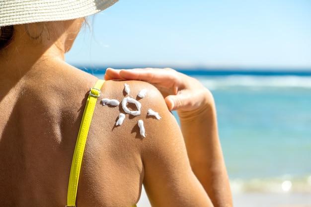 Vista traseira do jovem se bronzeando na praia com protetor solar em forma de sol no ombro dela.