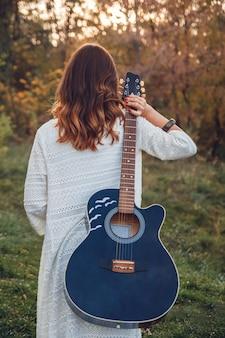 Vista traseira do jovem sentado na grama e tocando violão no parque ao pôr do sol.