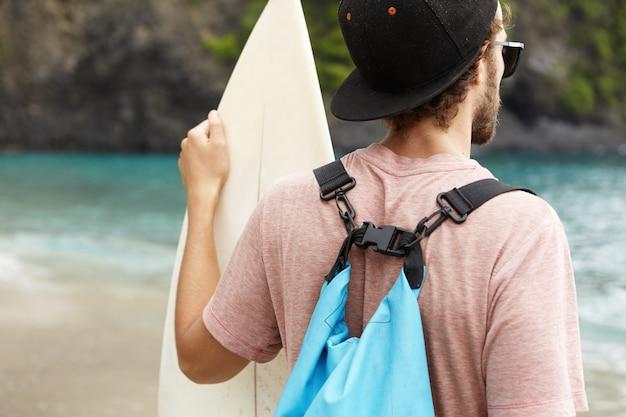 Vista traseira do jovem surfista iniciante barbudo vestindo snapback, óculos escuros e bolsa azul no ombro, segurando a prancha branca, olhando para a água azul do oceano