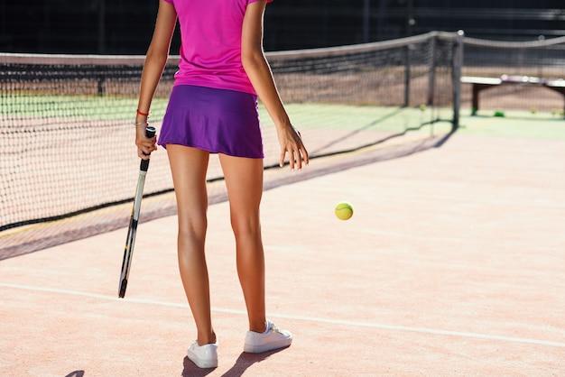 Vista traseira do jovem tenista bonito batendo a bola no chão enquanto caminhava na quadra no fundo por do sol.