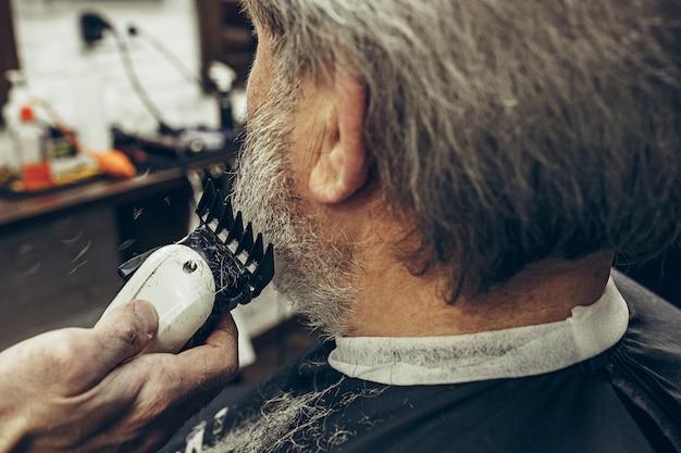 Vista traseira do lado do close-up homem caucasiano barbudo sênior bonito ficando barba aliciamento na barbearia moderna.