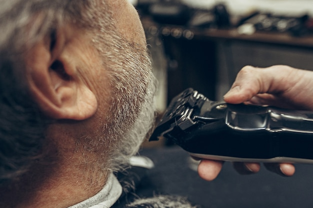 Vista traseira do lado do close-up sênior caucasiano barbudo homem bonito ficando barba aliciamento na barbearia moderna.