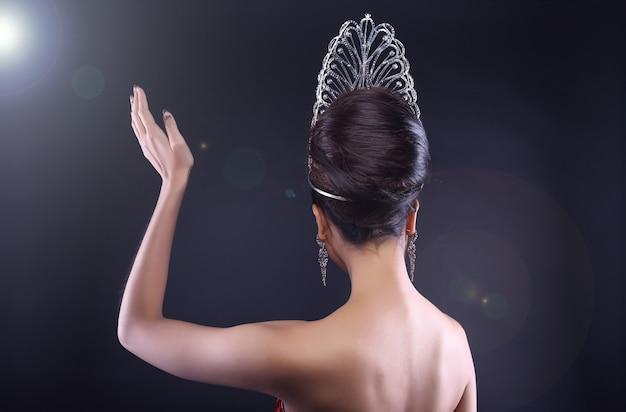 Vista traseira do lado traseiro retrato do concurso de beleza miss pageant com mão de onda de coroa de diamante