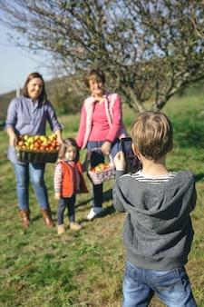 Vista traseira do lindo menino tirando uma foto com o tablet eletrônico para a família com maçãs orgânicas frescas em uma cesta de vime após a colheita. conceito de tempo de lazer em família.