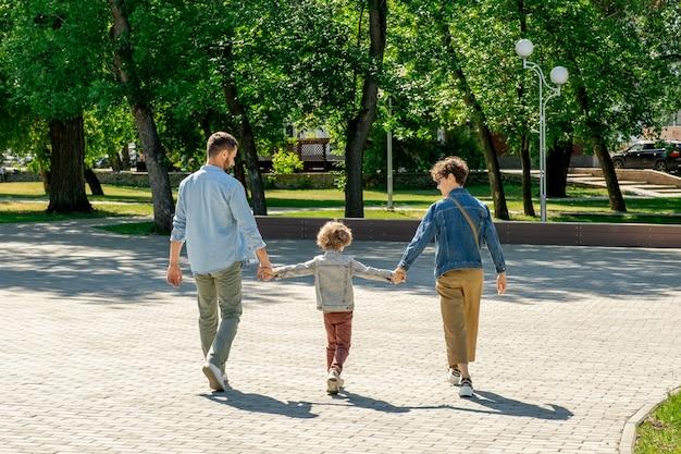 Vista traseira do menino em trajes casuais segurando os pais pelas mãos enquanto se move ao longo da estrada em um parque público durante uma caminhada em um dia ensolarado