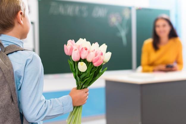 Vista traseira do menino segurando um buquê de flores para a professora