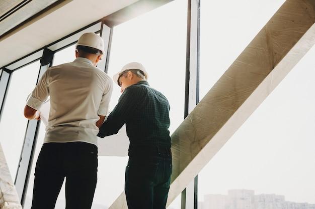 Vista traseira do mestre e do investidor inspecionando a obra do prédio em construção.