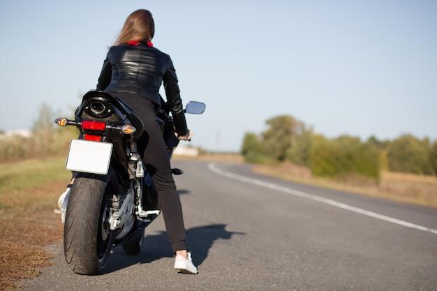 Vista traseira do motociclista feminina rápida veste jaqueta de couro, posa em moto, faz uma pausa após competições de corrida, espaço livre para o seu conteúdo publicitário na estrada