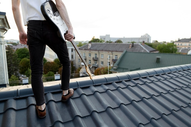 Vista traseira do músico masculino no telhado segurando uma guitarra elétrica